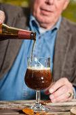 Alter mann, dunkles bier und käse im freien genießen. — Stockfoto