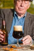 Starší muž tmavé pivo a sýr venku. — Stock fotografie