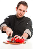 Young male cook with black jacket preparing raw ingredients. — Стоковое фото