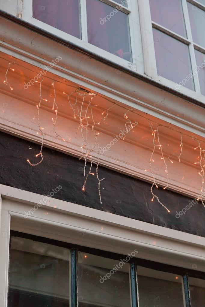 Christmas lights around window of a house. — Stock Photo #15686207