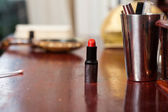 Red lipstick on wooden table. — Stock Photo