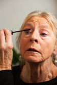 Senior woman doing make-up. — Stock Photo