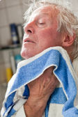 Senior man drying his face with towel. — Stock Photo