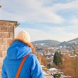 Woman from back looking over village in snow valley. — Stock Photo #18054199