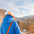 Woman from back looking over village in snow valley. — Stock Photo #18054315
