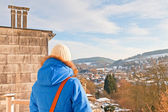 Woman from back looking over village in snow valley. — Stock Photo