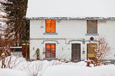 House with snow. Christmas lights in window. — Stock Photo
