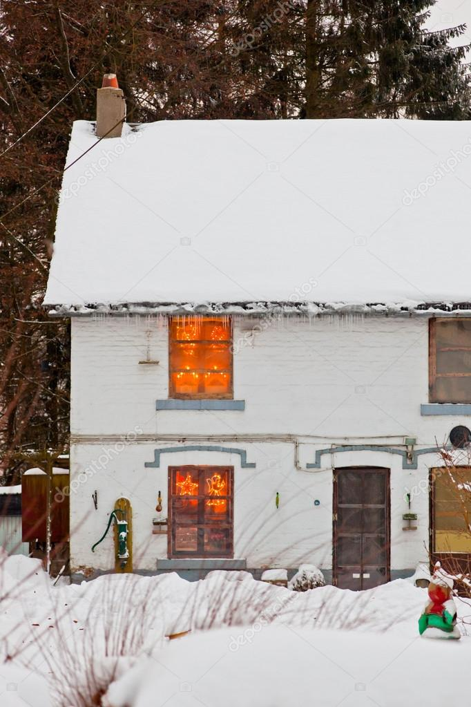 House with snow. Christmas lights in window. — Stock Photo #18054155
