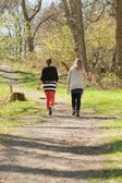 Two women walking on path in spring forest. — Stock Photo