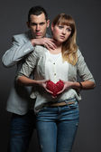 Mysterious young couple in love holding red heart. — Stock Photo