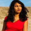 Indian girl with long hair dressed in red on the beach in summer — Stock Photo