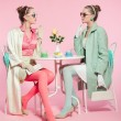 Two girls blonde hair fifties fashion style drinking tea. - Stock Photo