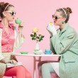 Two girls blonde hair fifties fashion style drinking tea. — Stock Photo #21448481