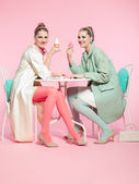 Two girls blonde hair fifties fashion style eating ice cream. — Stock Photo