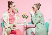 Two girls blonde hair fifties fashion style drinking tea. — Stock Photo