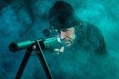 Snajper z brodą w czarny gospodarstwa pistolet. łapka. — Zdjęcie stockowe