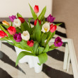 Colorful tulips in white vase on table in living room. — Stock Photo #23812059