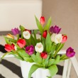 Colorful tulips in white vase on table in living room. — Stock Photo