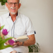 Senior man with glasses reading book in living room. — Stock Photo
