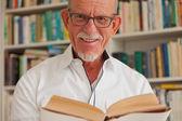 Uomo anziano con gli occhiali lettura libro davanti alla libreria. — Foto Stock