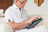 Starszy człowiek w okularach za pomocą tabletki na kanapie w salonie. — Zdjęcie stockowe