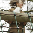 Funny young boy with long hair enjoying playground. - Stock Photo