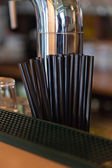 Black straws on bar near beer tap. — Stock Photo