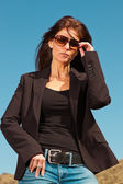 Smiling pretty brunette woman wearing brown sunglasses. Meadow w — Stock Photo