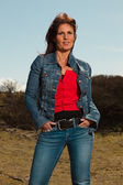 Smiling pretty brunette woman wearing jeans. Meadow with blue sk — Stock Photo