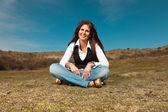 Smiling pretty brunette woman wearing jeans sitting in meadow wi — Stock Photo