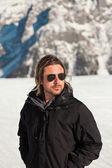 Ski man with sunglasses in rocky snow mountain landscape. — Stock Photo