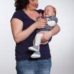 Happy mother holding her baby in her arm. Studio shot. — Stock Photo #24172515