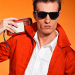 Stock Photo: Retro fifties style mwith sunglasses. Listening to radio. Reb