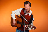 Retro fifties rock and roll singer playing accoustic guitar. Stu — Stock Photo