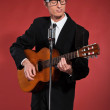 Retro fifties singer with glasses playing acoustic guitar. Studi — Stock Photo #24421321