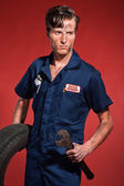 Retro fifties male car mechanic holding tool and tire. Studio sh — Stock Photo