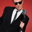 Retro fifties singer with vintage microphone and sunglasses. Stu — Stock Photo #24477529