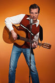 Retro fifties rock and roll singer playing acoustic guitar. Stud — Stock Photo