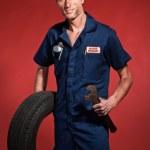 Retro fifties male car mechanic holding tool and tire. Studio sh — Stock Photo