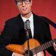 Retro fifties singer with glasses playing acoustic guitar. Studi — Stock Photo #24490469