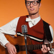 Stock Photo: Retro fifties musiciwith glasses playing acoustic guitar. Stu