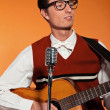 Retro fifties musiciwith glasses playing acoustic guitar. Stu — Stock Photo #24511213