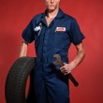 Retro fifties male car mechanic holding tool and tire. Studio sh — Stock Photo #24511217