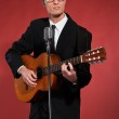 Retro fifties singer with glasses playing acoustic guitar. Studi — Stock Photo #24512329