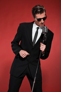 Retro fifties singer with vintage microphone and sunglasses. Stu