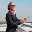 Business man with sunglasses outdoor on rooftop using tablet. — Foto de Stock