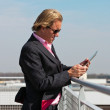 Business man with sunglasses outdoor on rooftop using tablet. — Stock Photo