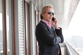 Business man with sunglasses calling with cellphone outdoor at o — Stock Photo