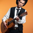 Retro country male guitar player wearing black suit and hat. Stu — Stock fotografie