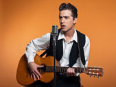 Retro country singer with guitar wearing black suit. Studio shot — Stock Photo